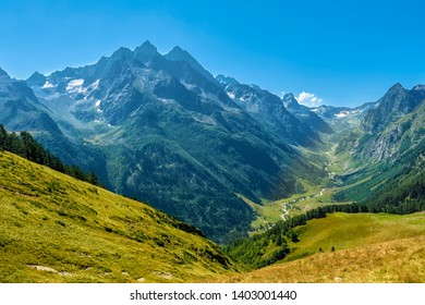 Hilly mountains against a cloudless blue sky. Snowy peaks. Coniferous forest in the foreground and the river in the distance. Tourism, travel, climbing, mountaineering. trek