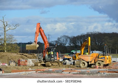 Hilperton, UK - February 21, 2015: Labourers work on a building site. The Wiltshire village is part of the UK's construction boom with the number of new homes being built up 10% since 2013.
