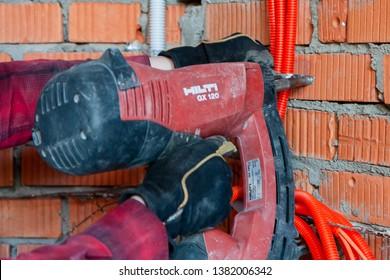 Hilti's nail gun driving a nail into a wall