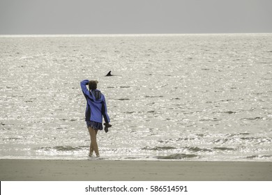 HILTON HEAD ISLAND, SC/USA - FEBRUARY 21, 2017: A young woman out for a walk along Coligny Beach shields her eyes from the bright morning sun while she watches a bottlenose dolphin swim by.