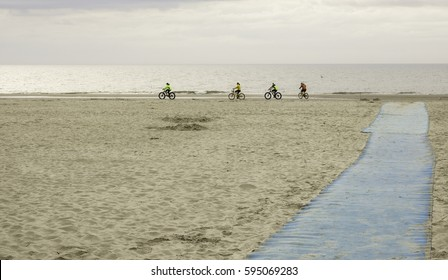 HILTON HEAD ISLAND, SC/USA - FEBRUARY 21, 2017: Near the end of a long blue walkway, four adult bicyclists in windbreakers and shorts set out on a morning ride along Coligny Beach.