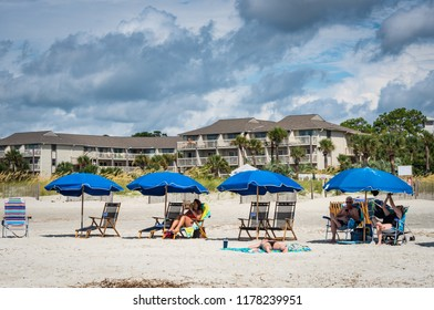 HILTON HEAD ISLAND, SC/U.S.A. - JULY 31, 2018: A photo of beach goers on Coligny Beach under beach umbrellas with condos and dramatic storm clouds in the background.