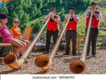 Him August mountain hut, by Ovronnaz village, Valais, Martigny-August 23, 2009: A band of three Swiss horn players entertain the guests at the lodge during a cheese and potatoes party, Switzerland