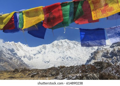 Himalaya Annapurna One mountain peak and prayer flags in blue sky, view from Annapurna base camp, famous trekking destination in Nepal.