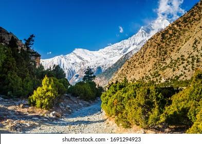 Himalaya mountain landscape near Chimang village with Mt. Dhaulagiri on the horizon. Annapurna circuit / Jomsom trek, Nepal.