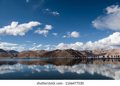 Himalaya mountain at Pangong Lake with blue sky, cloud, reflection on water and people