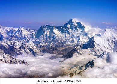 Himalaya mountains summits, Everest and Lhotse, with snow flags and clouds, view from plane. Himalaya range, Nepal, Asia.