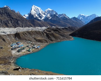 Himalaya scenery with a view of a blue lake, Gokyo village and a yak in the foreground.