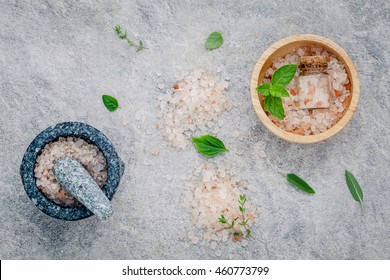 Himalayan pink salt in wooden bowl with peppermint ,sage,thyme,basil and oregano on stone background. Himalayan salt commonly used in cooking and for bath products such as bath salts.