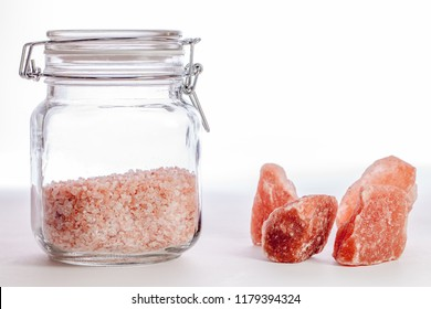 Himalayan rock salt. Pink crystal mineral salt in glass kitchen storage jar and as natural mined rocks. Nutrient-rich superfood. Organic condiment for healthy eating well-being.