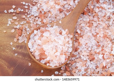 Himalayan rock salt in spoon and on wooden table
