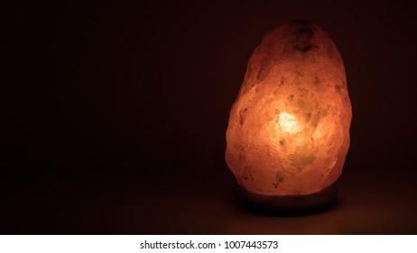 Himalayan salt crystal lamp, glowing in the dark.