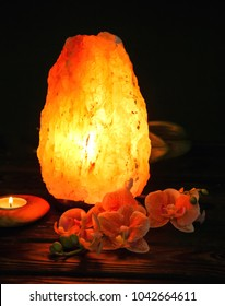Himalayan salt lamp, candle and flowers on table against dark background