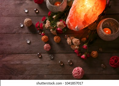 Himalayan salt lamp, candles and flowers on wooden table