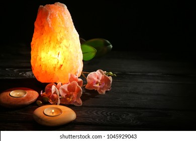 Himalayan salt lamp, candles and flowers on table against dark background