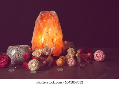 Himalayan salt lamp and flowers on table against dark background