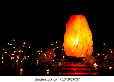 Himalayan salt lamp and garland on table against dark background
