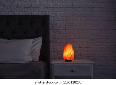 Himalayan salt lamp glowing on bedside table in dark room