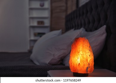 Himalayan salt lamp on bedside table against blurred background with space for text
