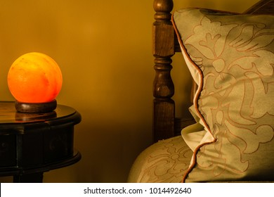 Himalayan salt lamp on night stand next to bed and large pillow