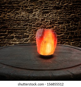 Himalayan salt as a lamp on an old wooden table in front of a stone wall