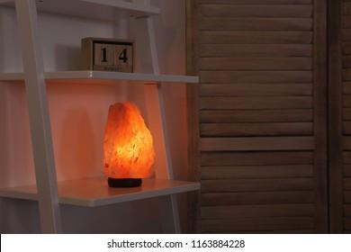 Himalayan salt lamp on shelf in dark room