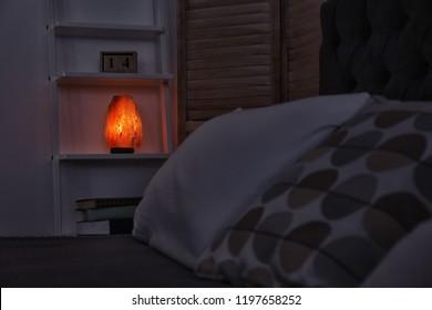 Himalayan salt lamp on shelf in dark bedroom