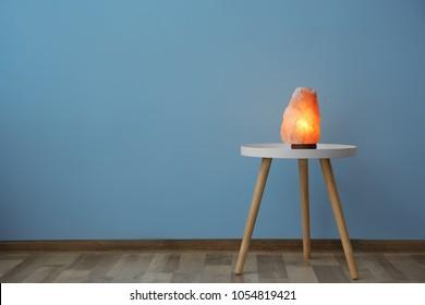 Himalayan salt lamp on table near color wall