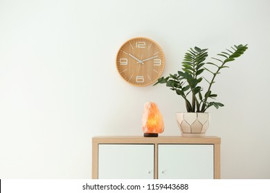 Himalayan salt lamp and plant on cabinet against white wall