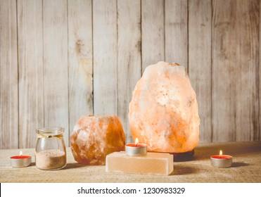 Himalayan Salt Soap bar, pink rock salt lamp illuminated and salt candle holder, with candle burning inside, jar with salt grains on wooden natural background, studio. Calming zen moods concept.