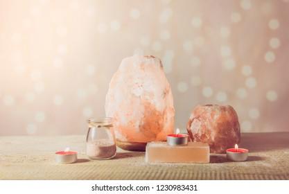 Himalayan Salt Soap bar, pink rock salt lamp turned on and salt candle holder, with candle burning inside, jar with salt grains on light bokeh background, studio. Calming zen moods concept.
