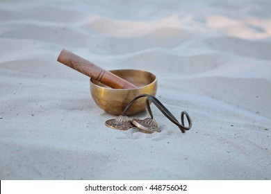 Himalayan Tibetan Singing Bowls, rin suzu gong and Karatalas on sand used worldwide for meditation, music, relaxation, personal well-being within Hinduism traditions to accompany kirtana or sankirtan