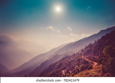 Himalayas landscape. Mountain range with trail in mist and clouds, blue sky with sun in the background. Everest Base Camp road. Trekking in Himalaya mountains, Nepal. Nature landscape. Vintage toning