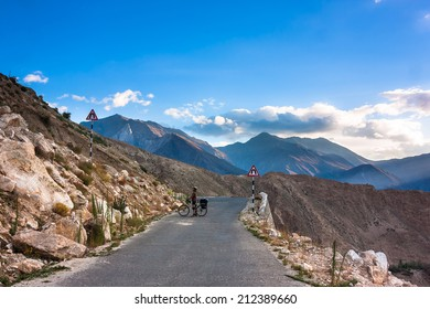 Himalayas landscape with mountains, lonley bicyclist, road and clouds