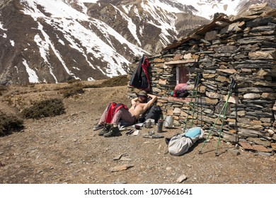 HIMALAYAS, NEPAL, 2013-03-22: male hiker taking rest next to abandoned house in the mountains under strong sun
