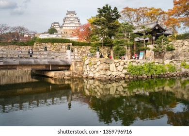 Himeji Castle, Hyogo Prefecture, Japan -November 8, 2018: People at the entry gate and the bridge over the inner moat surrounding Himeji Castle, also called 'White Egret Castle' in autumn in Japan.