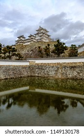 Himeji Castle reflected in moat against pastel sky