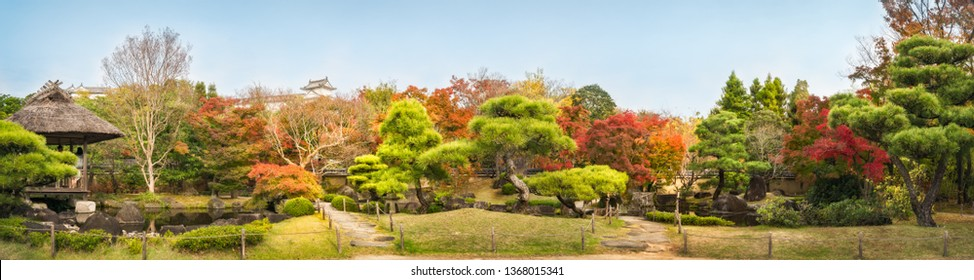 Himeji, Japan-November 8, 2018: Chinese style garden panorama in autumn at Koko-en Japanese Gardens with small stone bridges over the creek and with the rooftop of Himeji Castle in background in Japan