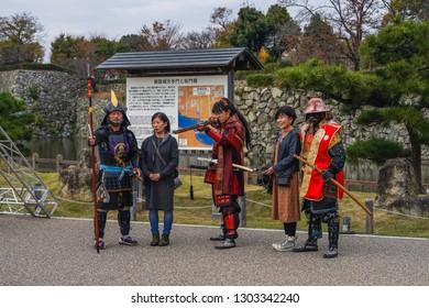 Himeji - Nov. 18, 2018: Japanese elder wearing samurai costume posing for photograph at Himeji Castle