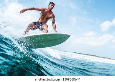 HIMMAFUSHI / MALDIVES - MARCH 10, 2019: Young surfer with lean muscular body rides the tropical wave