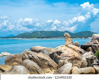 Hin ta, grandpa rock, giant stone look like penis (male genitalia) at beach in Samui island, Thailand, under cloudy blue sky