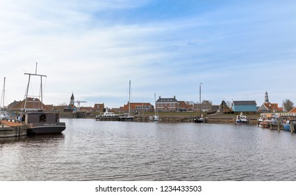 HINDELOOPEN, NETHERLANDS – MARCH 27, 2018: Old harbor with sluice, ships and buildings in Hindeloopen, Netherlands.