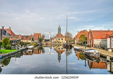 Hindeloopen, The Netherlands, November 4, 2018: sluice and adjacent sluice keepers house, bridge, boats and old houses reflect in the mirror-like water surface of a canal on a windless day