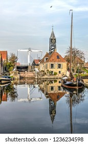 Hindeloopen, The Netherlands, November 4, 2018: the sluice keepers house with its tower, the adjacent bridge and a traditional barge reflect in the mirrorlike surface of the canal
