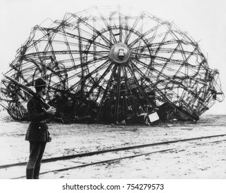Hindenburg wreckage guarded by a soldier at the Naval Air Station in Lakehurst, NJ. May 1937. The German passenger airship's twisted metal skeleton remains.