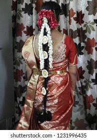hindu bride showing her back with long hair decorated with rose petals, jasmine flowers and lakshmi devi lockets