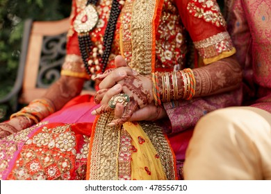 Hindu bride's hand painted with mehndi holds groom's arm