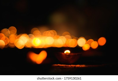 Hindu festival of lights. Clay diya candle illuminated. Traditional oil lamp on dark bokeh background, copy space.