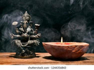 Hindu god Ganesha on black background. Statue on wooden table with a smoke of incense and a candle in a half of coconut. Copy space.