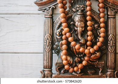 Hindu God - Ganesha with rudraksha rosary on white wooden background.